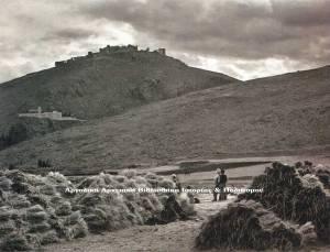 Άργος, σε πρώτο πλάνο Γεωργοί στις καθημερινές  ασχολίες τους, στο βάθος το φρούριο Λάρισα του Άργους και κάτω η Ιερά Μονή Παναγίας της Κατακεκρυμμένης ή Πορτοκαλούσας. Φωτογραφία του Ελβετού Φρεντερίκ Μπουασονά (Frederic Boissonnas), περίπου το 1903.