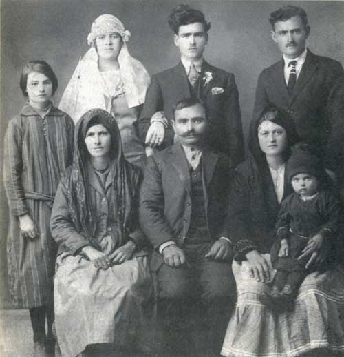 Αναμνηστική νυφική φωτογραφία, όπου ξεχωρίζουν τρεις τύποι αμφίεσης.  Οι καθστές γυναίκες με ντόπια φορέματα, η στολή της νύφης και οι «φραγκοφορεμένοι» άντρες με το γαμπρό.