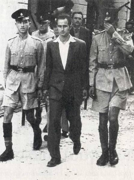 Ο Καραολής οδηγείται στο δικαστήριο. Θα καταδικασθεί σε θάνατο και θα εκτελεσθεί από τους Άγγλους δι' απαγχονισμού στις 10 Μαΐου 1956. Δημοσιεύεται στην εφημερίδα Καθημερινή. Σάββατο 24-Κυριακή 25 Μαΐου 2014.