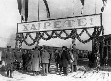 """Η είσοδος του στρατοπέδου Γκαίρλιτς . Διακρίνεται πλήθος επισήμων και η φρουρά της πόλης για να υποδεχτεί τον ελληνικό στρατό. Υπάρχει μια μεγάλη επιγραφή στα ελληνικά που γράφει """"ΧΑΙΡΕΤΕ"""" . Η φωτογραφία προέρχεται από το γαλλικό εβδομαδιαίο περιοδικό Le Miroir, τεύχος 153, 29 Οκτωβρίου 1916 και ο τίτλος της φωτογραφίας αποτυπώνει ανάγλυφα τα συναισθήματα των συμμάχων για την παράδοση του ελληνικού στρατεύματος, καθώς τιτλοφορείται «οι προδότες της Καβάλας εορτάζονται στη Γερμανία». Πηγή: Ίδρυμα Μουσείου Μακεδονικού Αγώνα."""