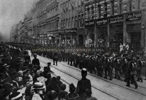 Οι ελληνικές δυνάμεις παρελαύνουν στο κέντρο της πόλης ενώ πλήθος κόσμου παρακολουθεί. Φωτογραφία από το εβδομαδιαίο περιοδικό Le Miroir, τεύχος 153, 29 Οκτωβρίου 1916. Πηγή: Ίδρυμα Μουσείου Μακεδονικού Αγώνα.