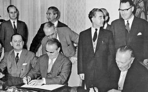 Βόννη, Νοέμβριος 1958. Καραμανλής και Αντενάουερ υπογράφουν διμερές ελληνογερμανικό πρωτόκολλο συνεργασίας ενώ ο Ευ. Αβέρωφ παρακολουθεί. Στις διαπραγματεύσεις για τις γερμανικές αποζημιώσεις έγινε προσπάθεια να μη διαταραχτούν οι ελληνογερμανικές σχέσεις κυρίως για οικονομικούς, αλλά και για πολιτικούς λόγους. Αρχείο: Ίδρυμα «Κωνσταντίνος Κ. Καραμανλής».