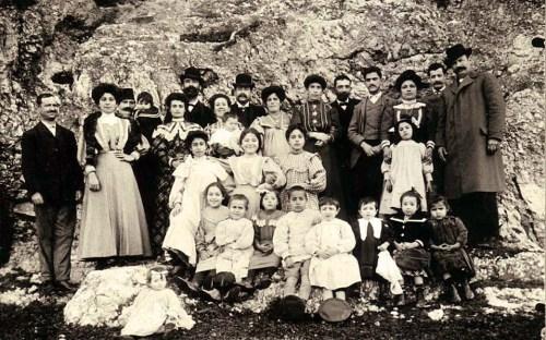 Ομαδική φωτογραφία των οικογενειών Γιουσουρούμ, Χαμπίμπ και Κοέν στο Θησείο, γύρω στο 1914. Στην πίσω γραμμή, τα πέντε παιδιά του Μποχώρ Γιουσουρούμ, Ηλίας (με μούσι και καπέλο), Χαΐμ, Ιάκωβος, Μωυσής, Νώε, με τις συζύγους και τα παιδιά τους, την τρίτη γενιά της οικογένειας. Στο κέντρο η γυναίκα του Νώε, Μαζαλτώβ (το γένος Χαμπίμπ), με τον νεογέννητο Ισαάκ στην αγκαλιά. Φωτογραφικό Αρχείο ΕΜΕ.