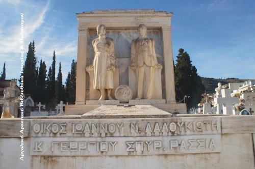 Νεκροταφείο Παναγίας, τάφος οικογένειας Ιωάννου Ν. Λαλουκιώτη (+1951). Πάνω σε κιβωτιόσχημη βάση, που καλύπτει τον τάφο, και μπρος σε κατασκευή που μιμείται κλασσική πρόσοψη οικίας (πεσσοί, επιστύλιο) τα ολόσωμα αγάλματα των Αρτεμισίας I. Λαλουκιώτη (1887-1942) και Ιωάννου Ν. Λαλουκιώτη (1882-1951). Ανάμεσα στα δυο αγάλματα κυκλική πλάκα με τις μορφές κατά κρόταφο και σε ελαφρό ανάγλυφο γέροντα με φέσι και γερόντισσας με τσεμπέρι. Υπογραφή: «Ε. ΤΖΩΡΤΖΑΚΗΣ ΕΠΙΟΙΕΙ». (Κώστα Δανούση, Έργα τηνιακών έντεχνων και λαϊκών γλυπτών στα νεκροταφεία της Ελλάδας, Αθήνα 1988). Φωτογραφία: Ηλίας Αντωνάκος, 2015.