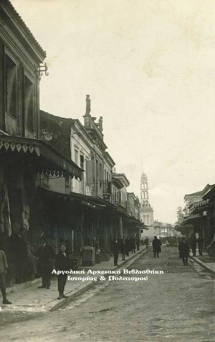 Άργος, οδός Ερμού, σημερινή Παν. Τσαλδάρη, περ. 1926. Στο βάθος το παλιό καμπαναριό του Καθεδρικού Ιερού Ναού Αγίου Πέτρου. Φωτογραφία: Γεώργιος Κυριακίδης (Απελλής).